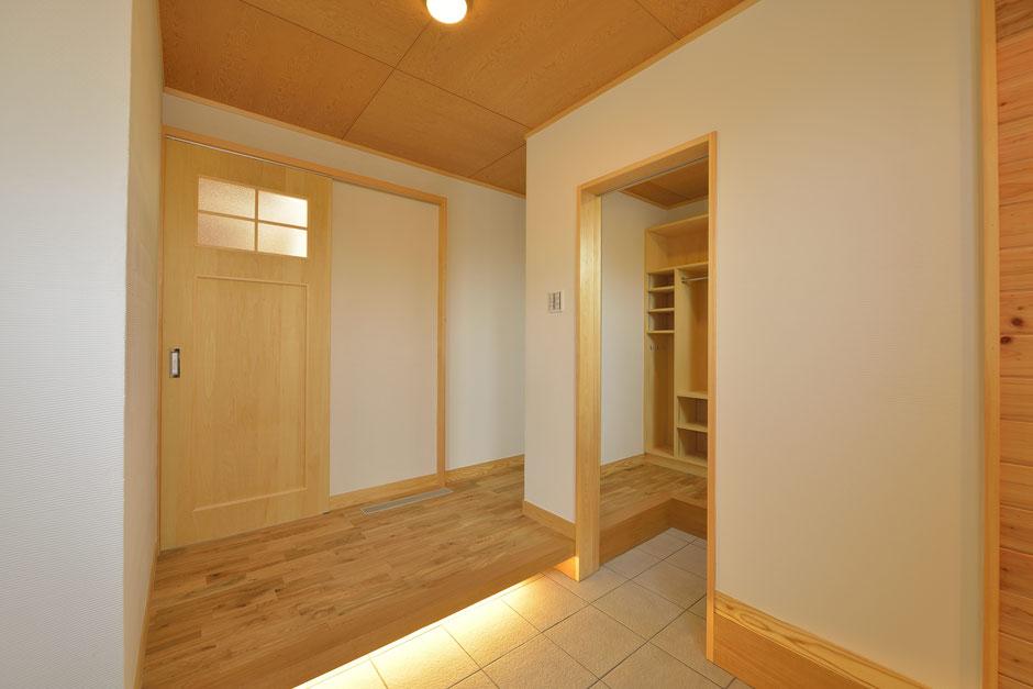 大きな吹抜けの家の玄関は框の下に照明がある