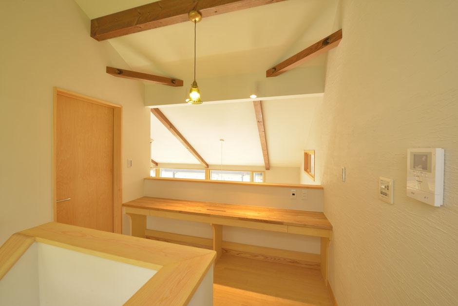 大きな吹抜けの家は2階のホールに木で造作したテーブルがある