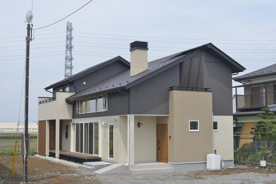 大きな吹抜けの家の外観は上下で色を塗り分けている