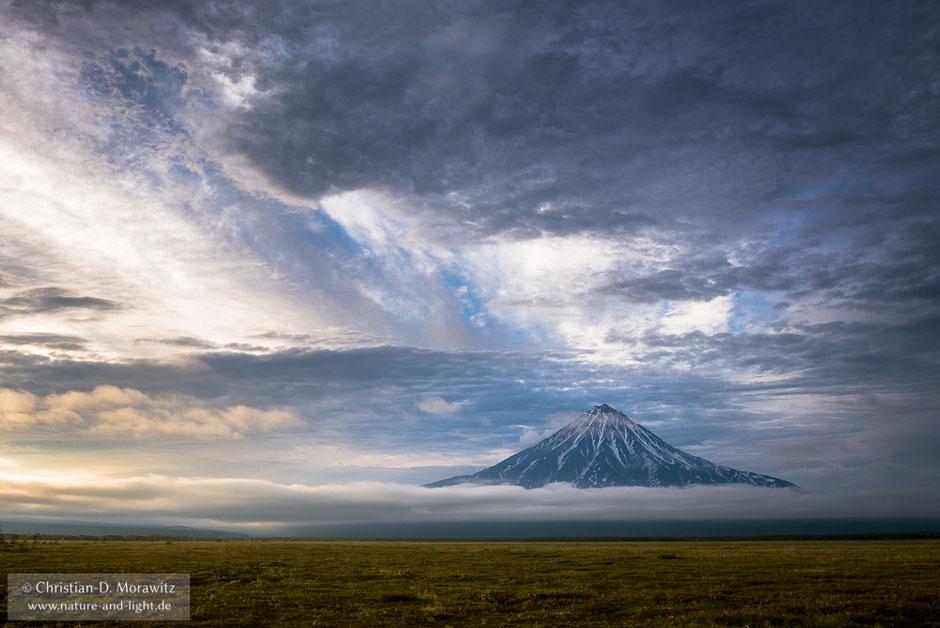 Der Kronotsky-Vulkan über den Wolken im Abendlicht