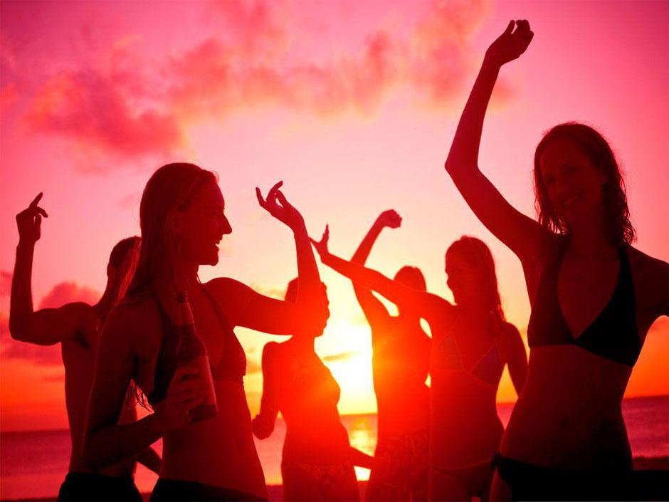 Menschen singen, tanzen und feiern auf einer Party am Strand und genießen die gute Musik - die Sonne und die Melodien durch den DJ