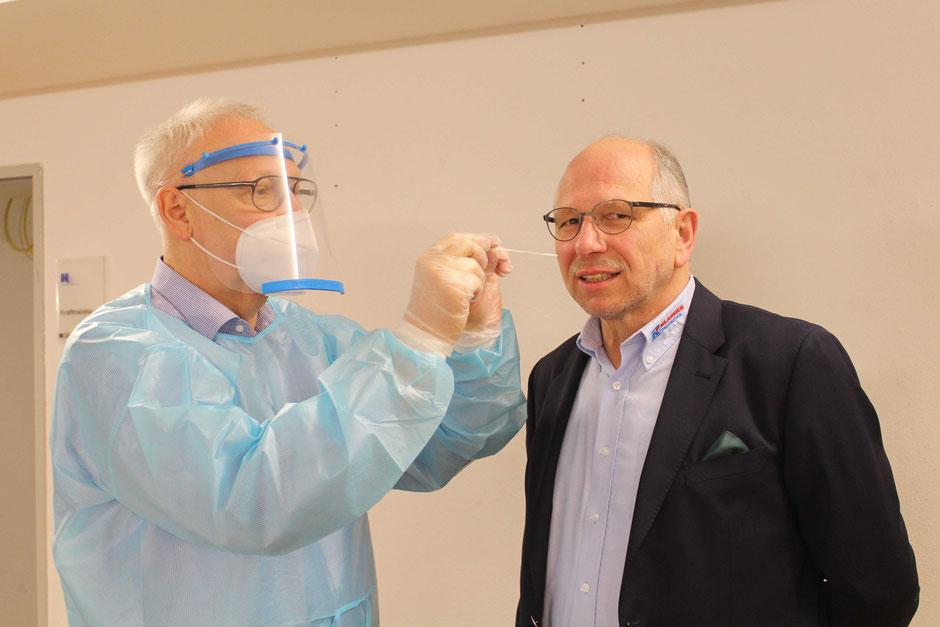 Schulleiter Hermann Hubing (l.) packt selbst mit an und führt im neuen Testzentrum der Holzfachschule Corona-Schnelltests durch. Hier testet er den Ersten Bad Wildunger Stadtrat Hartmut Otto (r.).