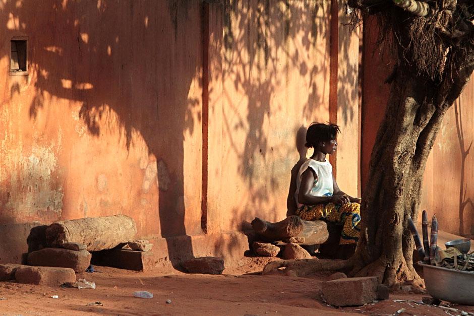 Femme togolaise assise sur un banc au crépuscule. Lomé. Togo.