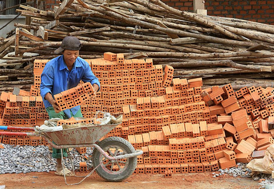 Ouvrier transportant des briques dans une brouette. Chantier de construction. Vang Vieng. Laos.