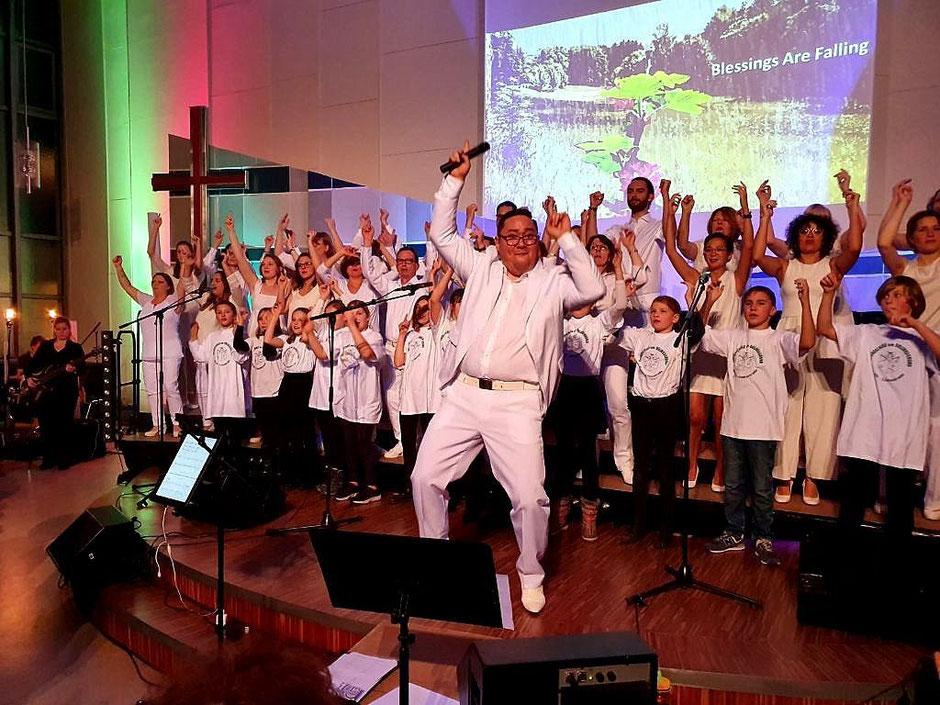 Hanjo, die Kinder des Unchained Mini Choirs und wir, der UGC, in weiß singend auf der Bühne