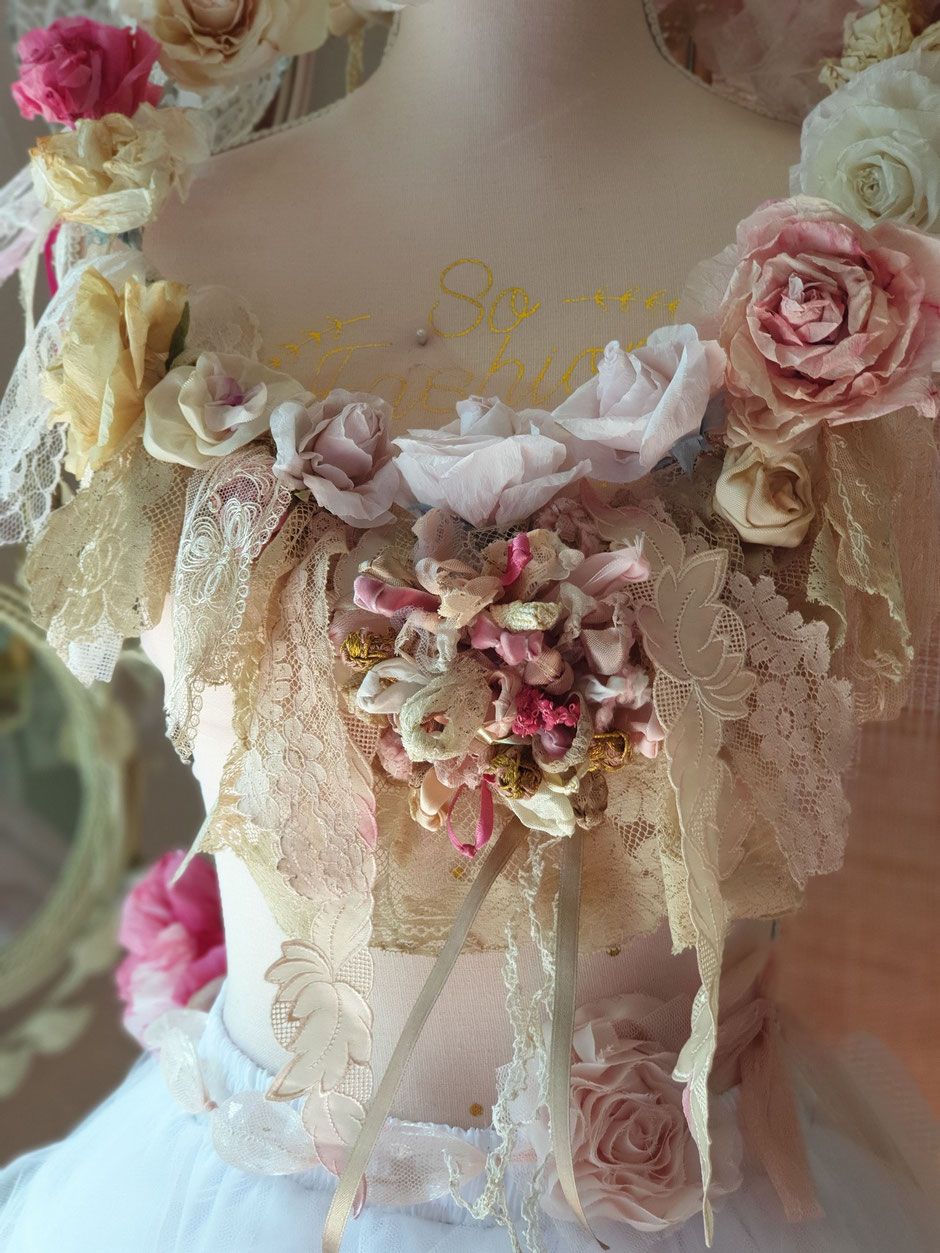 Nieuwe kransen of guirlandes met rozen van papier en enkele bijzondere rozen van stof, beiden met de hand gemaakt.