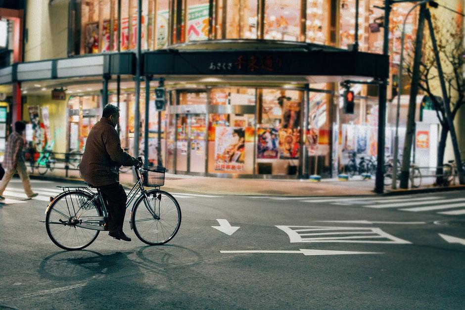 Homme à vélo d'occasion au japon durant la nuit.