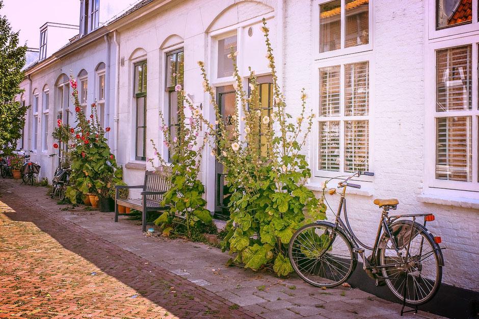 Vélo hollandais devant une maison blanche