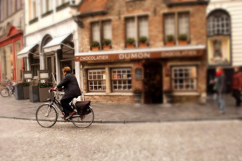 dame à vélo devant un chocolatier
