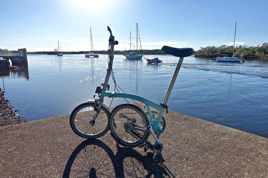 vélo bromption bleu sur un port de mer