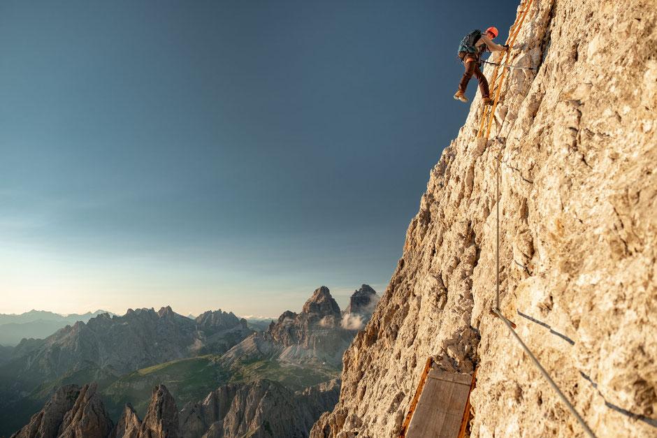 Climber on a vertical ladder on via ferrata Merlone in the Italian Dolomites.