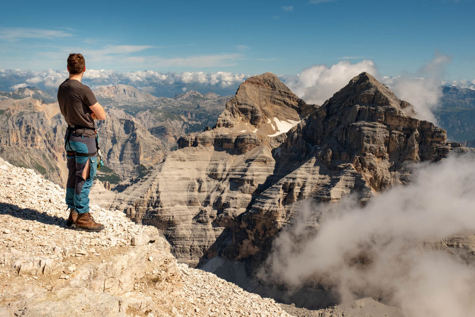 Hiker on the summit of Tofana di Rozes looking at the peaks of Tofana di Dentro and Tofana di Mezzo in the Italian Dolomites