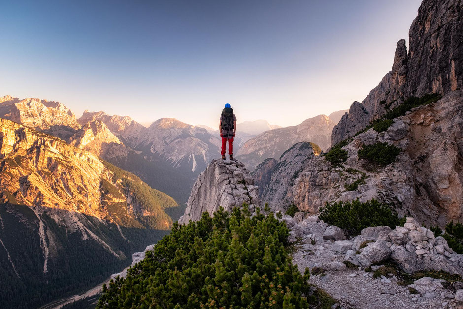 Climber standing on the top of an outcrop with the morning views of the Italian Dolomites. Via ferrata Michielli Strobel near Cortina D'ampezzo