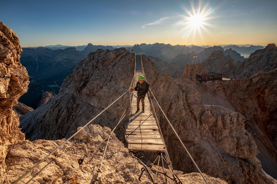 Hiker on the suspension bridge along the via ferrata Ivano Dibona in the Italian Dolomites. Behind you can view the Laurenzi refuge and the Tre Cime peaks