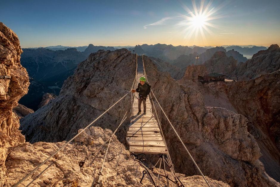 Hiker on the suspension bridge along the via ferrata Ivano Dibona in the Italian Dolomites. Behind you can view the Lorenzi refuge and the Tre Cime peaks