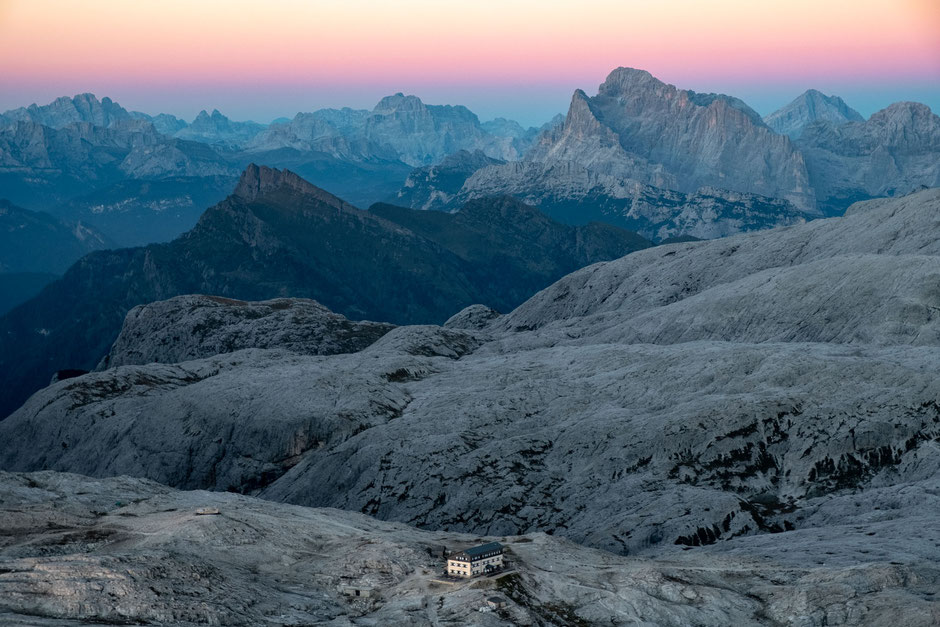 Rifugio Rosetta at dusk from the summit of Mount Rosetta. Monte Civetta can be seen in the distance