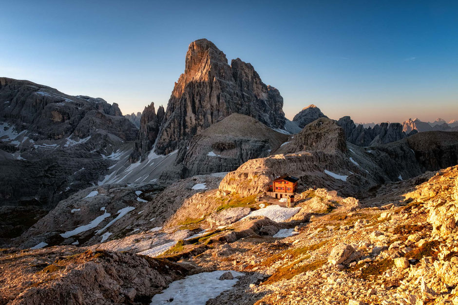 The tiny Buellelejochhuette dwarfed by the Zwölferkoffel in the Tre Cime National Park. Guide to staying in the mountain huts in the Italian Dolomites