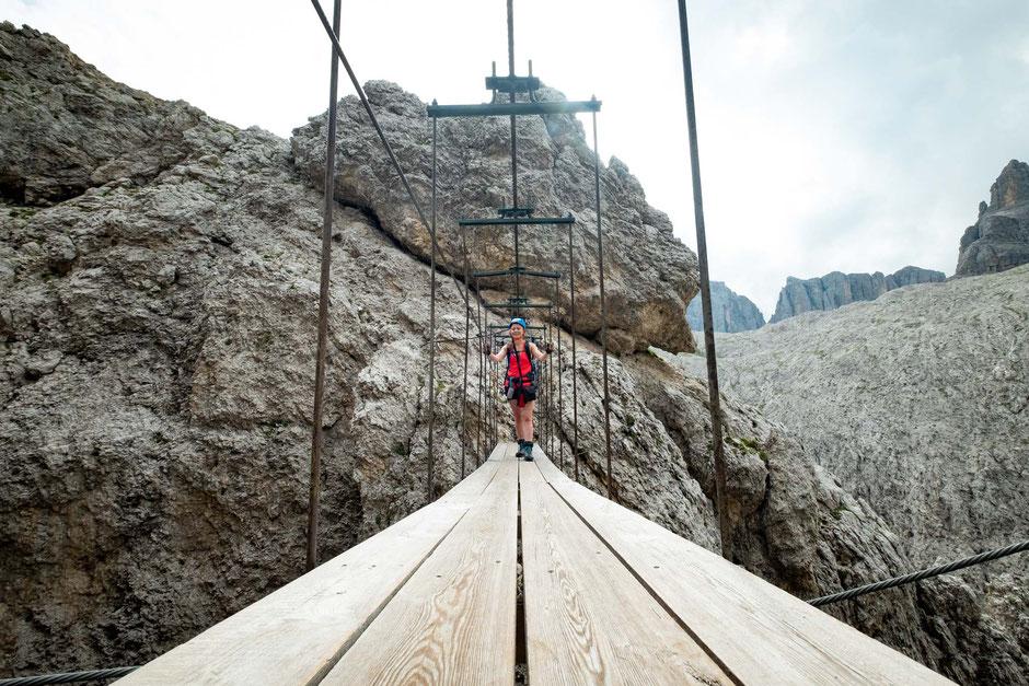 A climber on the suspension bridge between Torre Exner and Mur de Pisciadu on the via ferrata Brigata Tridentina