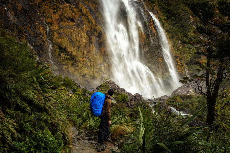 A hiker standing below Earland Falls on the Routeburn Track in New Zealand