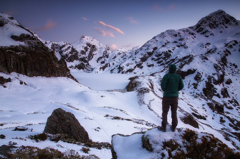 Harris Lake frozen over on the Routeburn Track in winter. Hiking guide to Routeburn trail in New Zealand