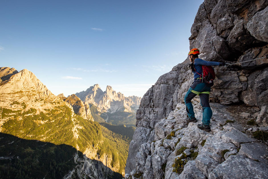 Climber looking towards Monte Cristallo from the route along the via ferrata Alfonso Vandelli in the Sorapiss range in the Italian Dolomites