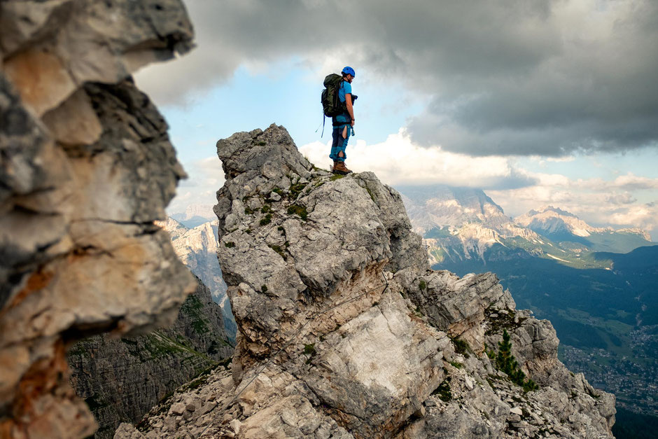Climber on one of the little summits along the via ferrata Ra Bujela in the Italian Dolomites