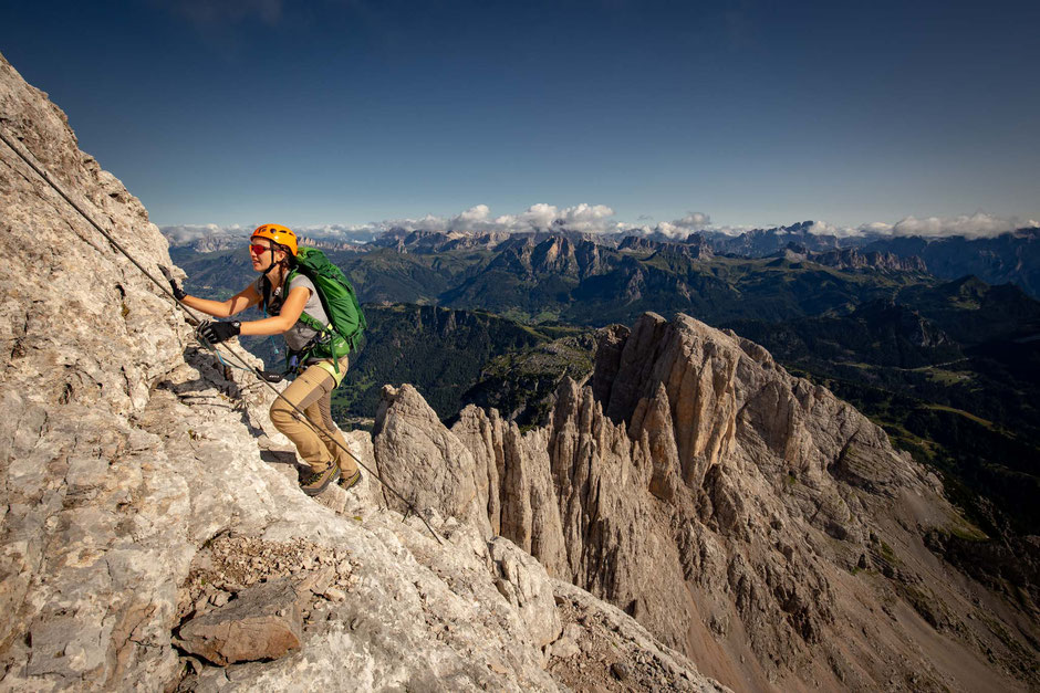 Female climber reaching the higher sections on the via ferrata Degli Alleghesi in the Italian Dolomites