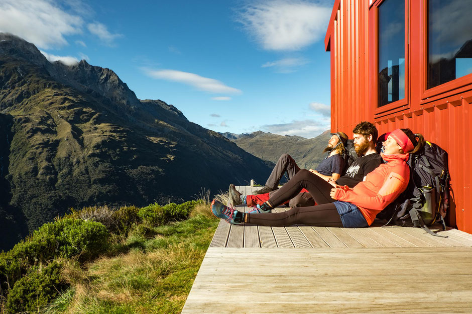 Hikers resting on the porch of Liverpool hut. Best hikes around Wanaka