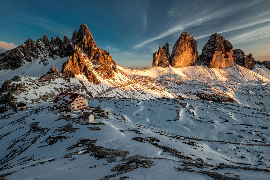 Rifugio Locatelli, Monte Paterno and the Three Peaks lighting up red at sunset after a late summer snowfall.