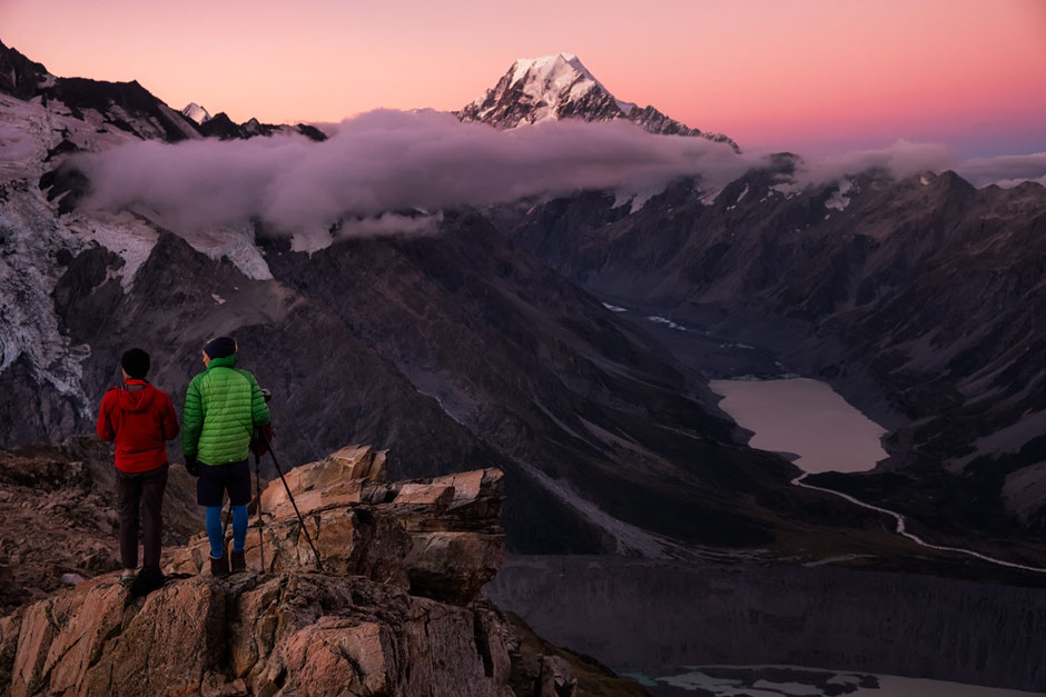 Hikers on Mount Oliver in Mount Cook National Park at dusk.