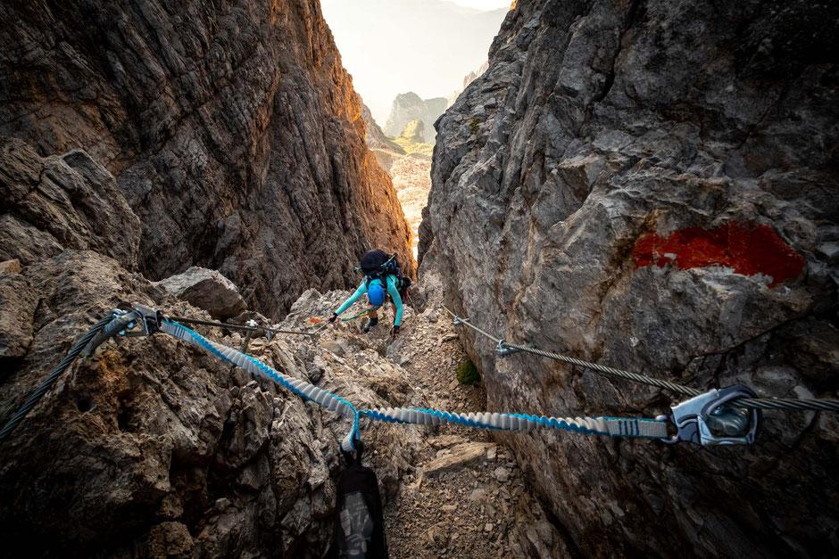 A climber in a narrow gully on the via ferrata Bocchette Alte in the Brenta Dolomites