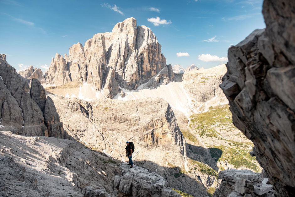 A hike traversing along the via ferrata Strada Degli Alpini in the Tre Cime NP in the Italian Dolomites with Croda dei Toni in the background