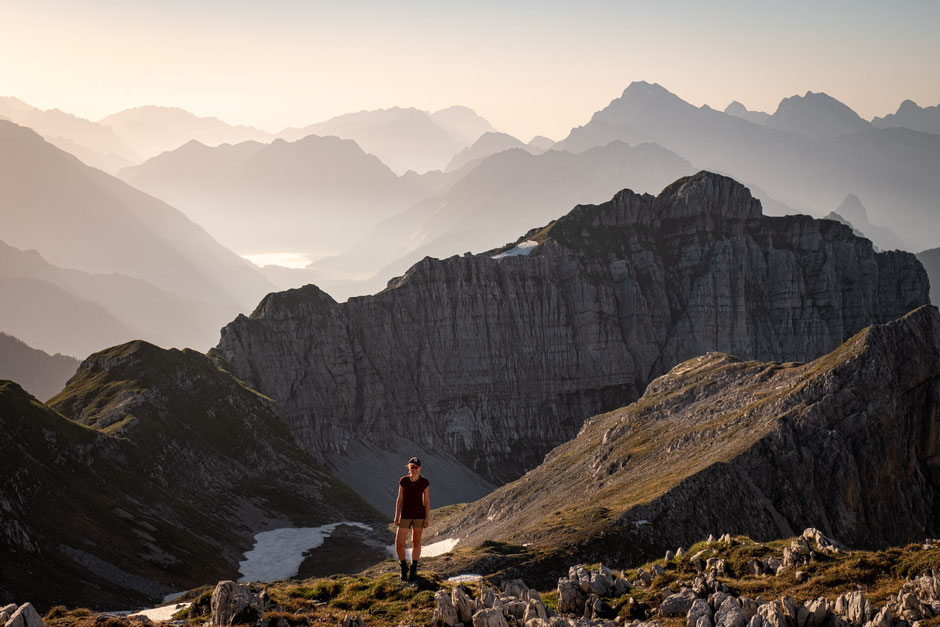 Hiker on a mountain top with beautiful layers of mountainous landscape in the background. Alta Via 1