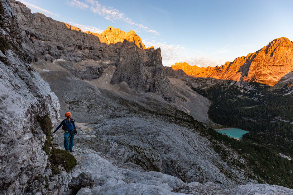 Early morning on the via ferrata Alfonso Vandelli. A climber looking down towards Lago di Sorapiss