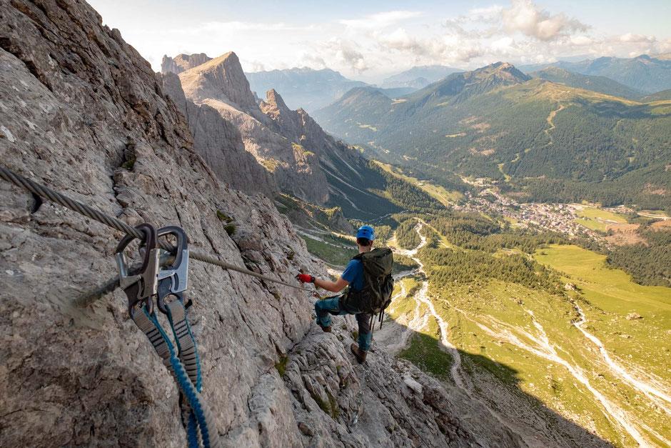 A climber looking down towards San Martino Di Castrozza from via ferrata Bolver Lugli in the Pale Di San Martino Group