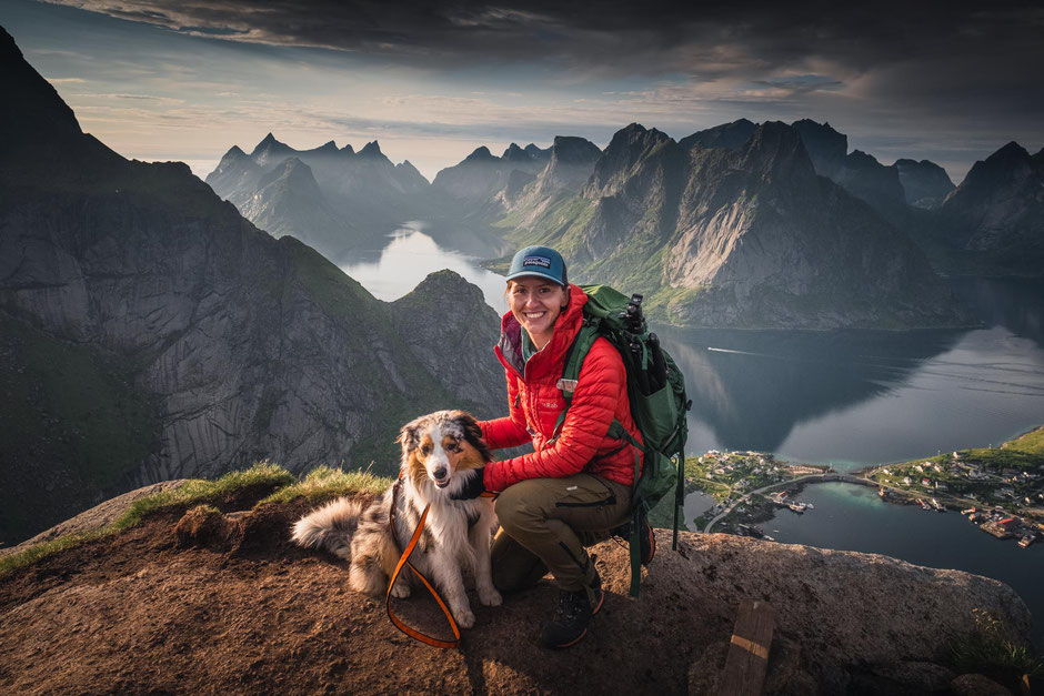 A hiker and a dog posing in front of the dramatic mountains on the top of Reinebringen, Lofoten Islands, Norway