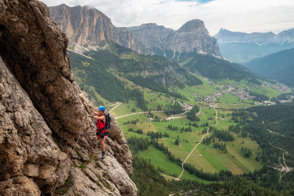 A climber on the via ferrata Brigata Tridentina with the views  of Sassongher and the towns of Colfosco and Corvara in the background