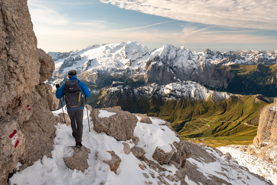A hiker descending from the summit of Piz Boé mountain. Marmolada - Dolomite's highest peak and its glaciers can be seen in the background.
