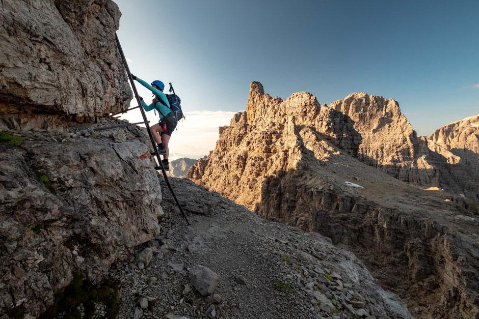 Female scaling a ladder along the via ferrata Bochette Alta in the Brenta group of the Italian Dolomites