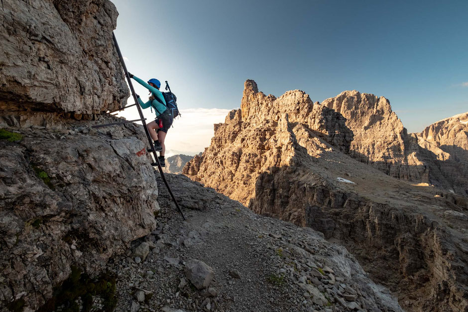 Female scaling a ladder along the via ferrata Bocchette Alte in the Brenta group of the Italian Dolomites