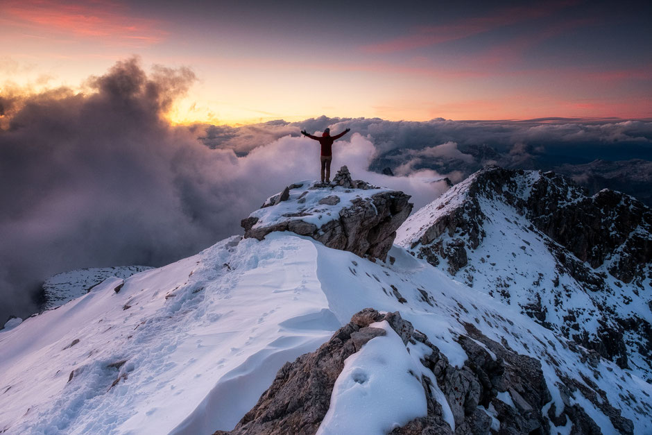 A hiker on the snowy summit of Piz Boé in the Italian Dolomites.