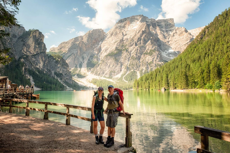Two backpackers standing near a fence with a dramatic lake and mountain view in the background. Lago di Braies - the start of Alta Via 1