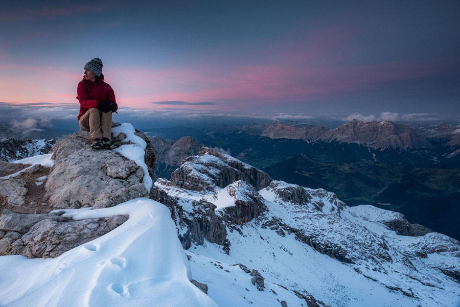 A hiker on the snowy summit of Piz Boé in the Italian Dolomites at dusk.