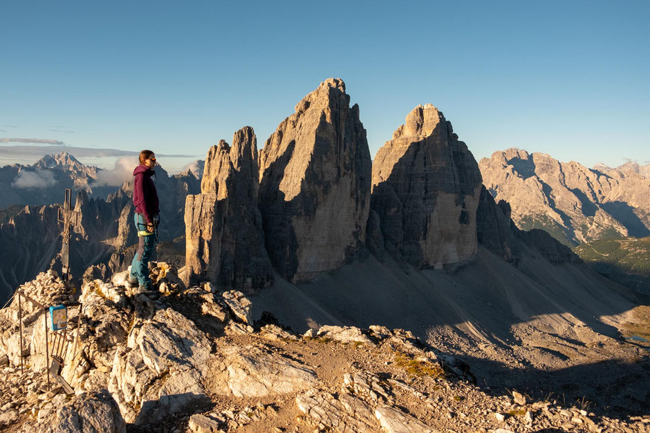 A hiker on the summit of Monte Paterno with Tre Cime in the background