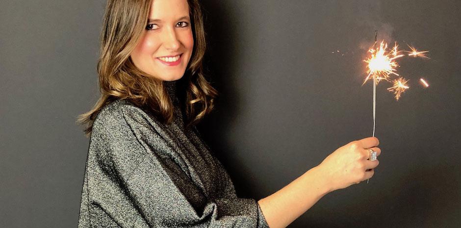 Mamabloggerin mit Wunderkerze an Silvester vor dunkler Wand