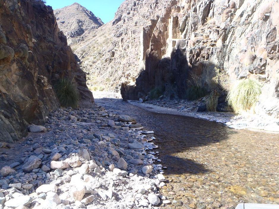 El río se abre paso entre montañas, dejando un estrecho lugar para pasar con las camionetas.