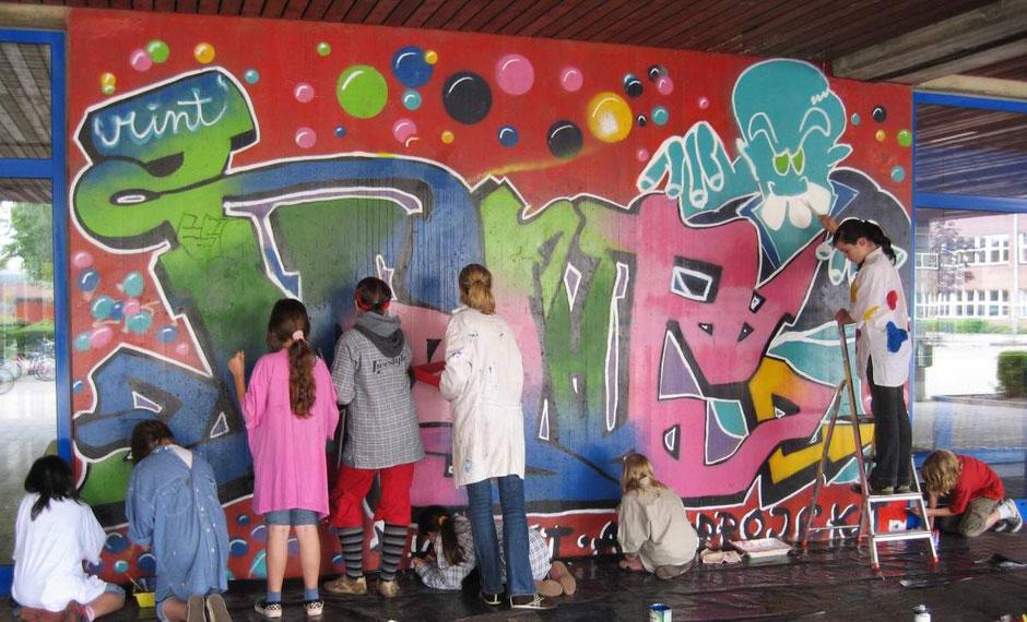 Schülerinnen und Schüler bei der Restaurierung des große Wandbildes zwischen unseren beiden Haupteingängen