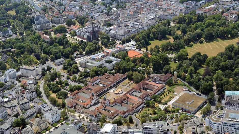 Das Sprudelhof-Areal, in das der Kurpark einfließt wird von der kurvigen Ludwigstraße eingefasst.  Darin, unterhalb der Dankeskirche, befindet sich der Ort der dritten Ernst-Ludwig-Buchmesse. Ein großes Parkdeck ist vorgelagert;  Foto: Ernst Stadler