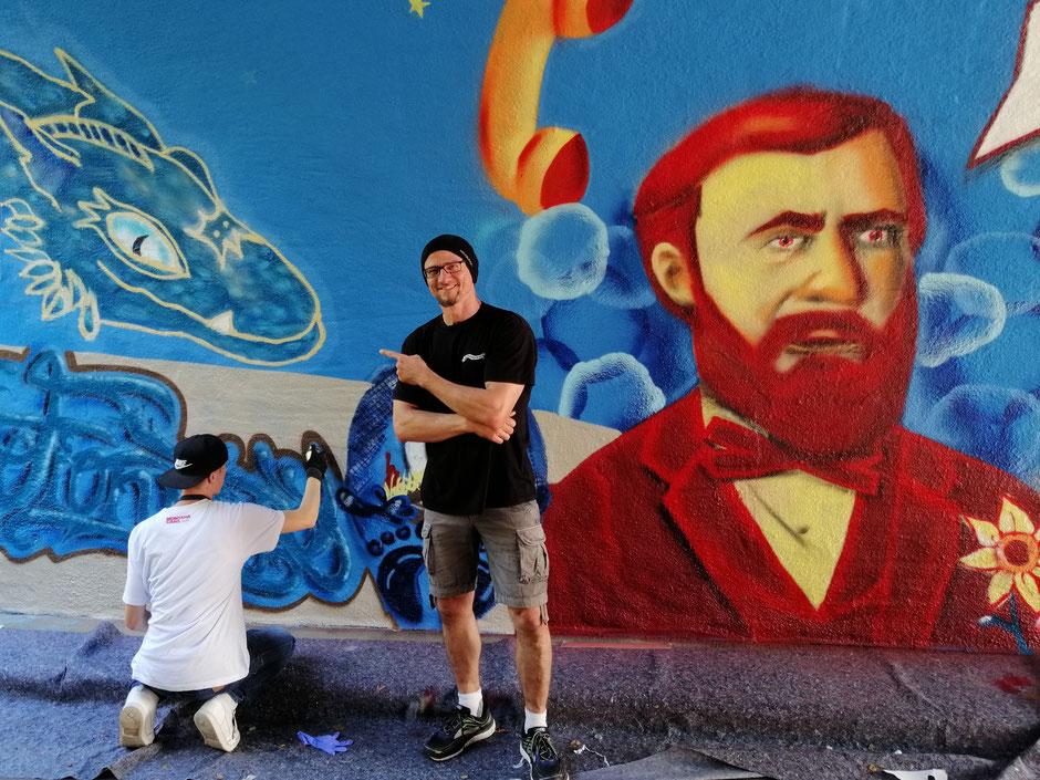 """Andreas Arnold vor dem Graffiti seines Drachen Fionrir, mir dem er in der Friedberger Fußgängerunterführung """"Zum Kühlen Grund"""" im Rahmen eines Jugendprojekts im Jahr 2019 geehrt wurde."""