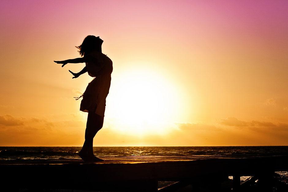 Frau streckt sich dem Sonnenuntergang entgegen